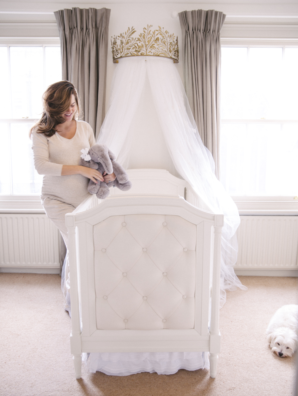 Upholstered crib in a cream and white nursery